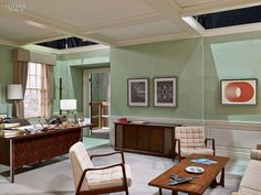 An office with white chairs, wooden desk and coffee table. Mint walls. Tour the Sets of Mad Men