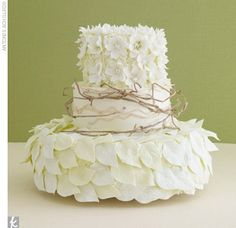 white and green wedding cake accented with sugar flowers, soft sugar-made branches, and leaves