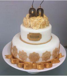 Bolo de frutas com decoração em renda dourada.