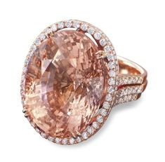 Set with an oval-shaped padparadscha weighing approximately 73.98 carats, within a brilliant-cut diamond surround, floral motif gallery and trifurcated shoulders, mounted in 18k rose gold, ring size 6¼. | Origin - Ceylon (Sri Lanka) | Estimate:  $1,035,223 – $1,552,835.