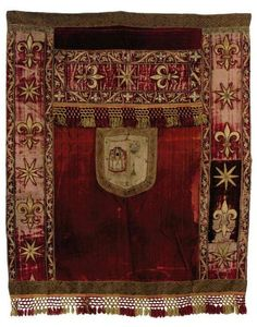 A BURGUNDY VELVET HANGING  FRENCH, LATE 17TH, EARLY 18TH CENTURY  Applied with stars and fleur-de-lis, worked in gilt metal threads, with a shield embroidered with a castle; together with two smaller, associated textiles