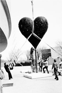 """Installation of Jim Dine's Exhibit at HMSG On the plaza of the Hirshhorn Museum and Sculpture Garden, February 1985, one of the two hearts of Jim Dine's bronze work """"Two Big Black Hearts"""" is being hoisted by workmen.."""