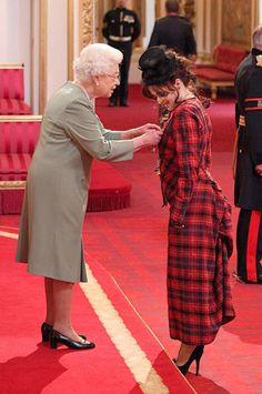 Helena Bonham Carter gets pinned by Queen Elizabeth. Tartan by Vivienne Westwood.