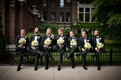 Groomsmen holding the bridesmaids' bouquets... love it!
