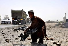 AFGHANISTAN, Kandahar : An Afghan child lifts a piece of mangled wreckage from a vehicle at the scene of a blast in Kandahar on September 14, 2013. AFP PHOTO/Siddiqullah ALIZAI