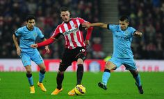 Sunderland player Connor Wickham (c) is challenged by Sergio Aguero (r) during the Barclays Premier League match between Sunderland and Manchester City at Stadium of Light on December 3, 2014 in Sunderland, England.