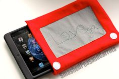 """Etch-a-Sketch ipad Cozy  2 pieces of red fleece measuring 24"""" x 10"""" 1 piece of gray fleece measuring 9.5"""" x 6"""" 2 small circles of white fleece 1 7.5 inch piece of velcro (mine was red to match) red thread white thread black thread (for any words you want to stitch) disappearing ink pen sewing machine rotary cutter and mat"""