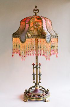 This is a hand painted, detailed, ornate early 1900s metal lamp base which holds a Haight-Ashbury Beehive lampshade in colors of pink, green and teal.