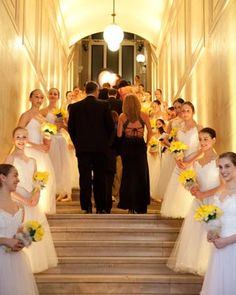 Ballet students hold the ball's signature blooms, daffodils, as they greet guests
