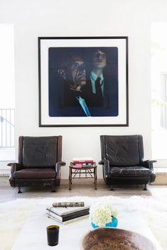 Oversized artwork/photograph with leather armchairs in white living space