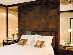 Mirrors on either side, bedside tables with small lights, matching back drop at head of bed, framing on mirror to match.