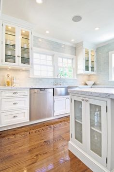 White and gray kitchen. Carrara marble countertops, glass cabinet doors, gray subway tile backsplash.