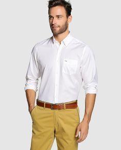 Camisa de manga larga, de color blanco. Tiene el cuello americano, los puños redondeados y lleva un bolsillo en el pecho.