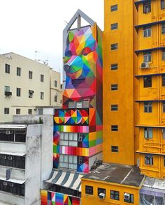in the sham shui po district of hong kong artist okuda san miguel has added the rainbow thief to the façade of a narrow residential building for hong kong walls 2016. @okudart  see more on #designboom #art #streetart by designboom