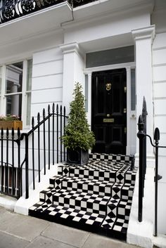 27 Pictures of Black Front Doors (Front Entry) Standing over a vibrant checker patterned set of steps, this black door features a plethora of subtle brass hardware, framed in smoked glass. Front Stairs, Front Entry, Black Front Doors, London Townhouse, Front Door Design, White Houses, House Front, Entrance, House Design
