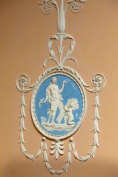 Relief plasterwork in white on Wedgewood blue background on the pink wall of the Staircase at Claydon, Buckinghamshire