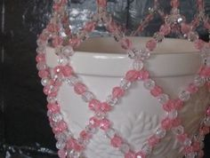 Beaded Plant Hanger in Pink: This plant hanger is made with 20 lb. fishing line and clear and pink round beads with white seed beads on the tassels. This plant hanger is 24 inches long with a 9 1/2 inch flower pot ( flower pot not included) This plant hanger is pictured with a 6 inch flower pot....