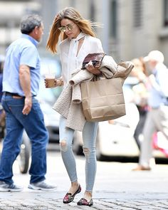 Caffeine fix:The socialite, 31, kept things casual in a cream chiffon semi-sheer blouse with neck tie detailing, which she teamed with ripped skinny jeans to showcase her slender shape