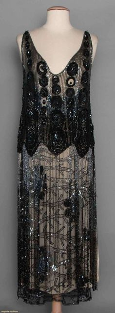 """SEQUINED & BEADED TABARD, c. 1925 Black net, shoulder to hip area covered w/ black & gunmetal sequins in dense circular patterns, stylized branch & blossom pattern below hip to hem is partially concealed by 20+"""" long beaded fringe, B 34""""-36"""", L 48"""""""