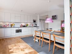 A family of five calls this kitchen home in Stockholm, Sweden and along with the white cabinets and wood floors, they've incorporated lots of color, like the pink light and LEGO box on the counter to hold utensils.