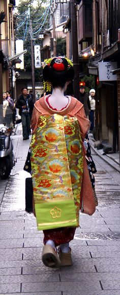 This is a perfect photo of a Maiko. Notice how everyone she's walking towards has stopped to look at her! That's what a striking sight these ladies are. Also notice: long obi, hair ornaments, high shoes, all hallmarks of the Maiko. Japanese Textiles, Japanese Kimono, Japanese Art, Geisha Japan, Geisha Art, Yukata, China, Japon Tokyo, Kyoto Japan