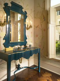 """Carefully orchestrated vanity and mirror combo with hand-painted wallpaper. The colors are beautifully """"off"""" - deep azure lacquer with gold trim, soft peach background wallpaper, shutters the same color - sophisticated choices."""