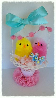Two cute chenille chicks are sitting in a vintage favor basket. The basket is decorated with pom pom trim, ribbon, and a crepe paper ruffle.   basket is