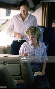 Diana, Princess Of Wales, Sitting On Board A Royal Australian Air Force Plane Which Is Refueling In Fiji Before Continuing To Australia. The Princess And Commander Brian Robertson (the Australian Equerry To Prince Charles For The Royal Tour) Are Enjoying An Impromptu Birthday Celebration. The Princess Has Been Given A Slice Of Cake.