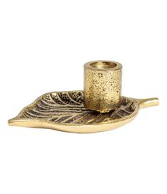 Gold-colored. Candlestick in antique-finish metal with a leaf-shaped base. Diameter of candle holder approx. 3/4 in., size of base 4 x 5 1/2 in.
