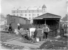 Poikia kaivolla Viidennellä linjalla 1911. Vesijohdot on vedetty Kallion talojen pihoille, mutta kaivoja ei hylätty, sillä vesijohtovesi oli maksullista. Taustalla uusi vuokratalo Kaikukujan ja Pengerkadun kulmassa. Kuva: Signe Brander.