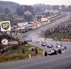 Graham Hill ( holds on to the lead in his BRM heading up Eau Rouge for the first time at Spa. FIA Formula One World Championship, Circuit de Spa-Francorchamps, 1965 Belgian Grand Prix Jackie Stewart, Michael Schumacher, Ferrari, Maserati, F1 Racing, Road Racing, Le Mans, Formula 1, Ayrton Senna