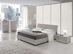 En esta habitación hay una cama muy amplia blanca y gris. Hay una messilla de noche con sobre una pequeña lámpara blanca. Hay también muchos muebles y una alfombra blanca y un espejo.  Mi cuarto preferido!