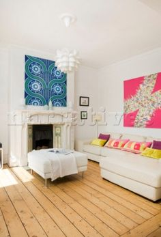 White leather ottoman and colourful artwork in living room of Manchester family home  England  UK
