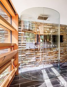 A wall of local stone adds a rugged ambience to the glass-enclosed shower in the master bath of a contemporary North Carolina home designed by Gluck + Partners.