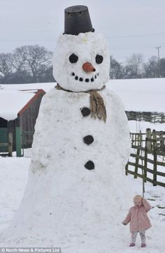 Kara-Louise Richardson, 16-months-old, stands next to a giant 15ft snowman built in her garden at Sundown Farm, Bishop Auckland, Co. Durham. The structure took eight people over three hours to build. UK wants people to build snowmen to avoid flooding as compacted snow melts more slowly.