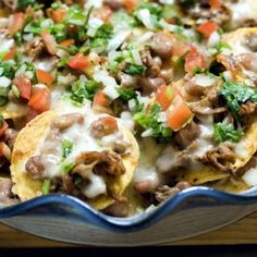 Cowboy Nachos Recipe with pinto beans, ground black pepper, Tabasco Pepper Sauce, minced garlic, jalapeno chilies, canola oil, beef brisket, pan drippings, sauce, pico de gallo, tortilla chips, grated jack cheese, guacamole, sour cream