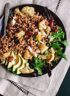 A satisfying salad featuring warm whole grains, caramelized cauliflower, greens and avocado. This vegetarian salad will pack well for lunch!