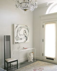 contemporary gray foyer entry design with lucite acrylic console table, tall slat back chair, owl umbrella stand, white & black abstract art