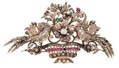 Broche devant de corsage, de la segunda mitad del siglo XVIII. En oro de 9K, diamantes tallas rosa y rosa coronada, 4,89 cts y vidrios rojos y verdes. Representando un cesto con aves y motivos florales.