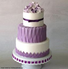 The color purple and flower decorations for wedding cake. Four-tiered ombre purple blossoms with fondant flowers and lace detail, 5-tiered Wedding Cake with
