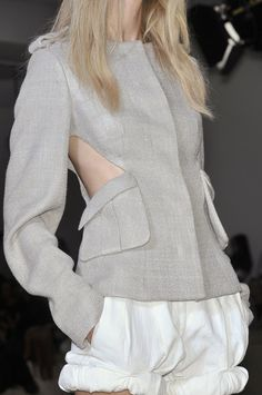 Structured grey jacket with cut out detail alongside the pockets - cutaway fashion; cool fashion design details