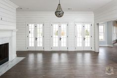 Transitional living room features walls clad in white shiplap framing a wall of French doors.