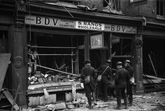 London. Shopkeeper sweeps up broken glass from his shattered show window after a bombing raid.