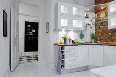 Beautiful white kitchen with exposed brick walls.