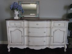 Pretty dresser in an antiqued ivory, light chippy distressed finish. Stained top. Five dovetailed drawers with decorative glass knobs. Three middle drawers are bowed. Two cabinets with a shelf in each. Scalloped bottom. Love the crystal knobs.