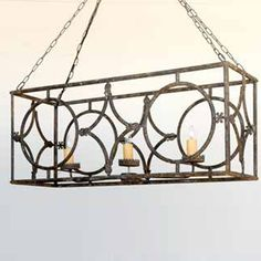 Durable metal with an aged finish crafted in a rectangular open box style. Three metal crowns hold beeswax candle covers. Circle and diamond detail. Forty two inches of hanging chain included. Aged fi...