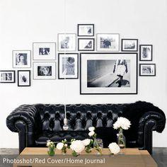 Schwarzes Chesterfield-Sofa und Bilder in Petersburger Hängung