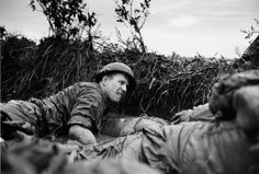 Vietnam War August 14, 1966: Pinned down by Viet Cong machine gun fire, a U.S. medic looks over at a seriuosly wounded comrade as they huddle behind a dike in a rice paddy, near Phu Loi, South Vietnam, August 14, 1966.