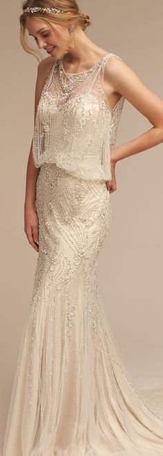 Take a step back to the 20s in the glamorous Art Deco period exquisite blouson beaded gown. One-of-a-kind beading bejewels, an illusion neckline, cascading over tulle overlay. Covered buttons run up the back for a feminine accent. Ivory gown