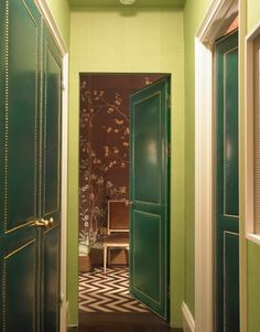 """Green Hallway- Redd revved up hallway walls with vivid olive India tea paper from de Gournay and doors with Edelman leather in garden green and nailhead trim. """"If they get beat up, they'll only look better,"""" he says."""